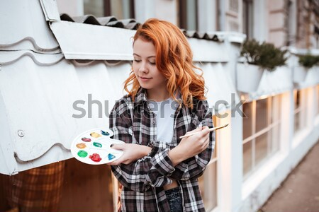 Cheerful young lady painter with red hair walking on street Stock photo © deandrobot
