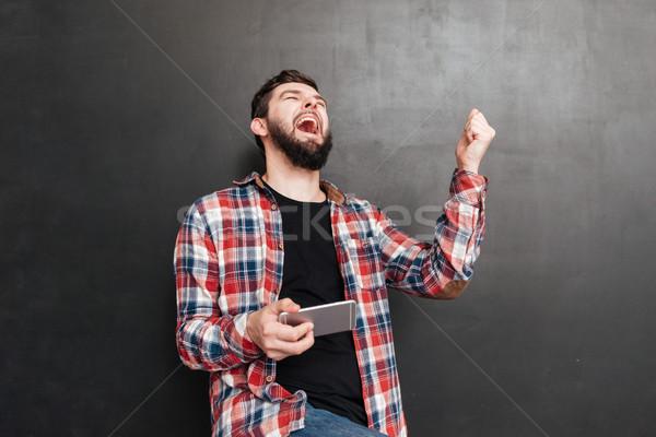 бородатый молодым человеком смеясь смартфон серый Сток-фото © deandrobot