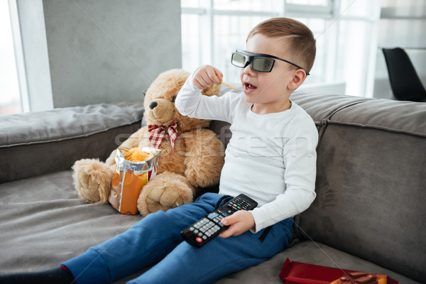 Boy wearing 3d glasses sitting on sofa with teddy bear Stock photo © deandrobot