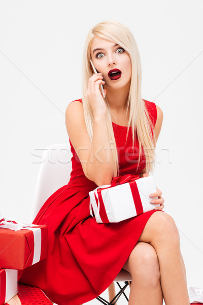 Woman in red dress with presents talking on mobile phone Stock photo © deandrobot