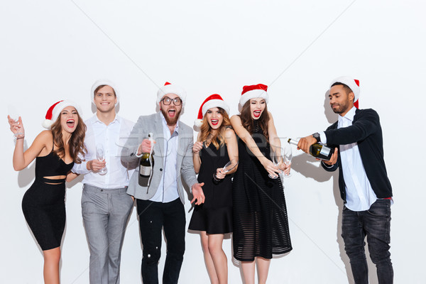 Smiling people in santa claus hats pouring and drinking champagne Stock photo © deandrobot