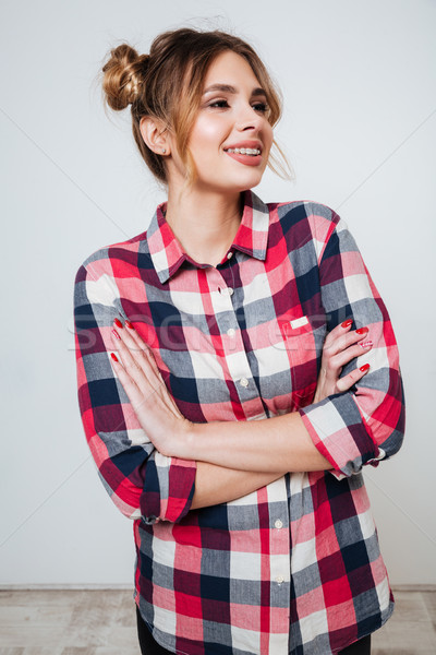 Happy young woman in plaid shirt standing with arms crossed Stock photo © deandrobot