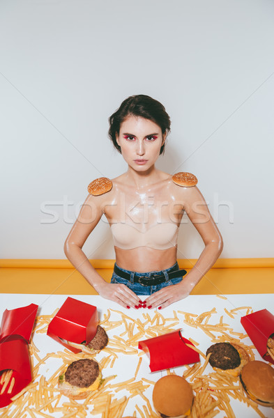 Beautiful woman with buns imitating shoulder straps eating fast food Stock photo © deandrobot