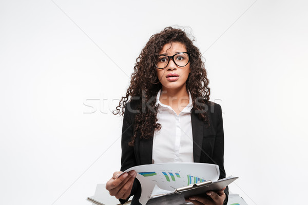 Shocked african business lady wearing glasses reading gazette Stock photo © deandrobot