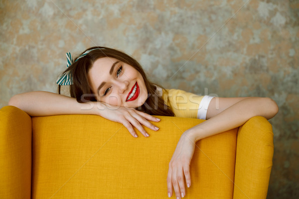 Smiling happy pin up girl laying on chair Stock photo © deandrobot