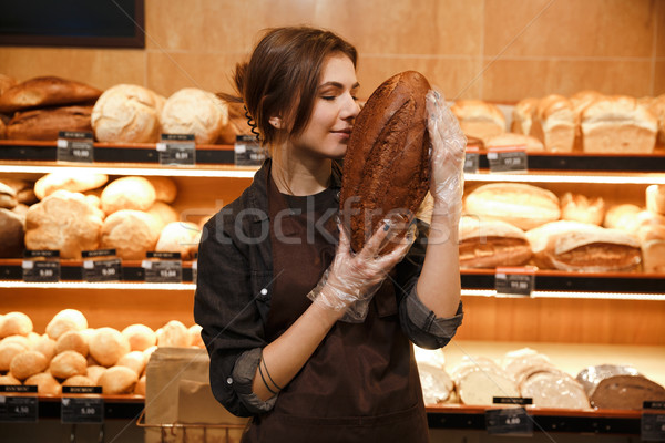 Happy woman in supermarket choosing and smells bread. Stock photo © deandrobot