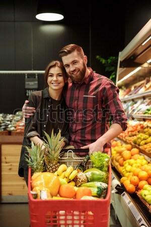 Cheerful young loving couple in supermarket Stock photo © deandrobot