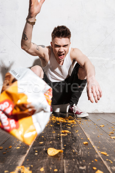 Angry young man throwing packet of potato chips in camera Stock photo © deandrobot