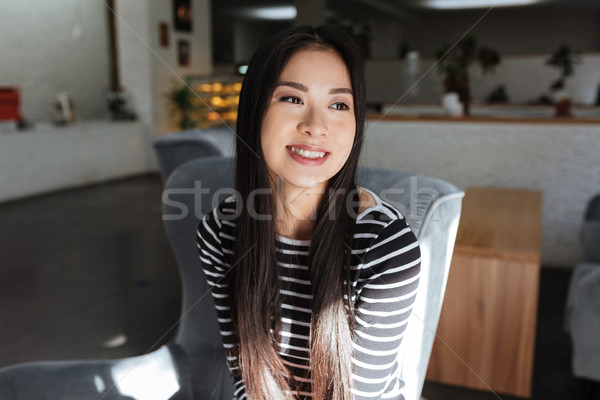 Elégedett ázsiai nő ül büfé pulóver Stock fotó © deandrobot