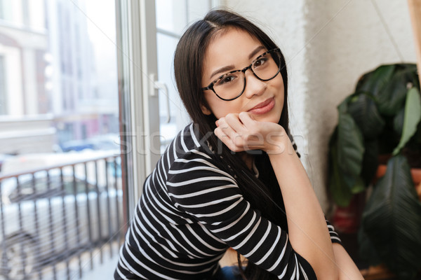 Side view of Young Asian woman sitting on windowsill Stock photo © deandrobot