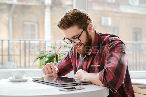 Happy bearded young man using tablet computer. Stock photo © deandrobot