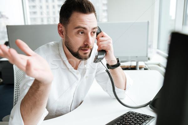 Uncomprehending man talking on phone Stock photo © deandrobot