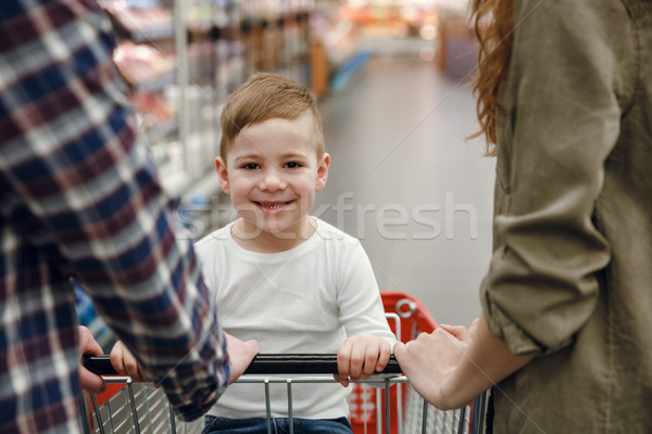 Young boy sitting on shopping trolley Stock photo © deandrobot