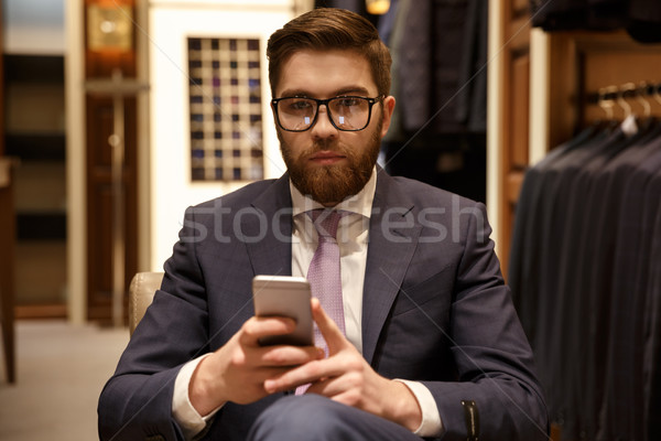 Serious man in suit and eyeglasses holding mobile phone Stock photo © deandrobot