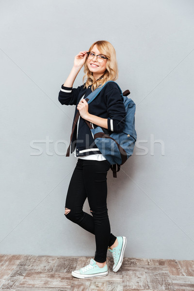 Stock photo: Pretty young lady student over grey wall. Looking at camera.