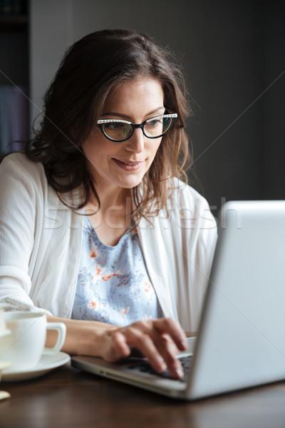 Sorridente mulher madura trabalhando laptop tabela Foto stock © deandrobot