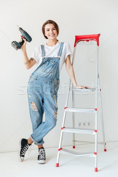 улыбающаяся женщина дрель лестнице изолированный белый Сток-фото © deandrobot