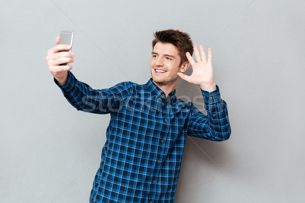 Young man greeting with somebody while making videocall or selfie Stock photo © deandrobot