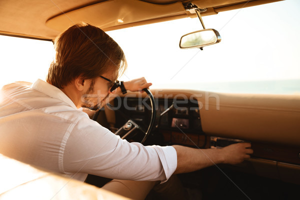 Young man driver turning on stereo system Stock photo © deandrobot