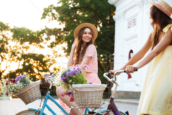Two happy smiling women in hats riding vintage bicycles Stock photo © deandrobot
