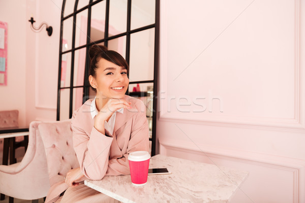 Smiling pretty girl drinking coffee while sitting at the cafeteria Stock photo © deandrobot