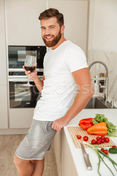 Vertical picture of smiling bearded man standing sideways Stock photo © deandrobot