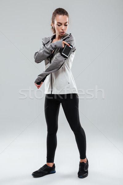 Full length image of a sports woman using smartphone Stock photo © deandrobot