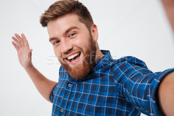 Happy bearded man in checkered shirt making selfie Stock photo © deandrobot