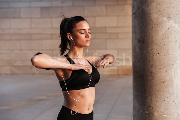 Serious young sports lady standing with earphones outdoors. Stock photo © deandrobot