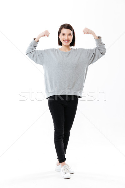 Full length of a happy girl standing and showing biceps Stock photo © deandrobot
