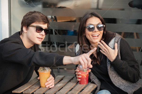Stock photo: Happy young lady sitting outdoors with her brother drinking juice.