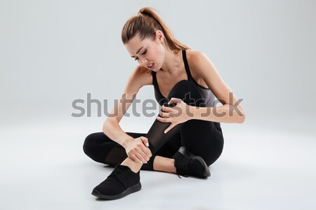 Sad young sportsman sitting isolated have a painful feelings. Stock photo © deandrobot