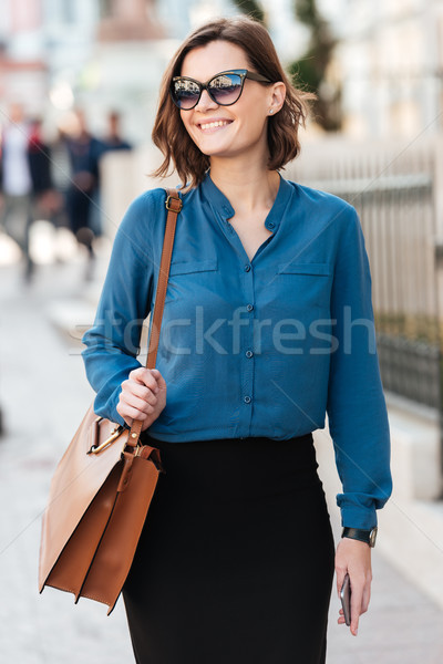 Smiling lovely woman in sunglasses on a street Stock photo © deandrobot