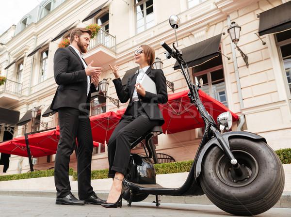 Full length image of smiling business couple posing near motorbike Stock photo © deandrobot