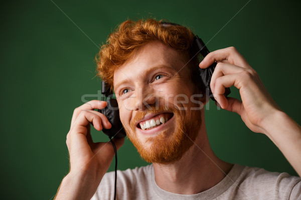 Young curly readhead bearded man is enjoying listening to music Stock photo © deandrobot