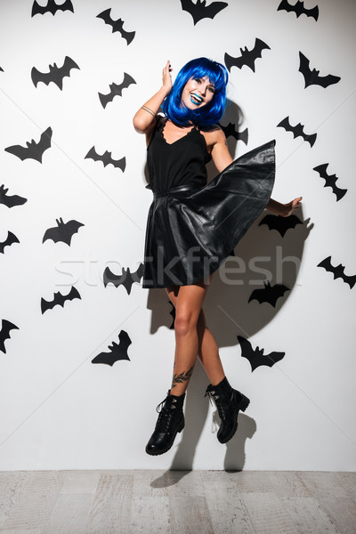 Emotional happy young woman in witch halloween costume Stock photo © deandrobot