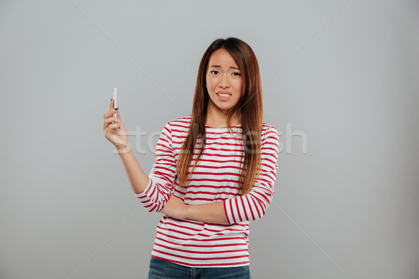 Confusi giovani asian signora parlando telefono Foto d'archivio © deandrobot