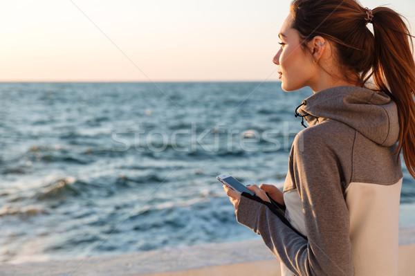 Hátulnézet csinos sport nő tart okostelefon Stock fotó © deandrobot