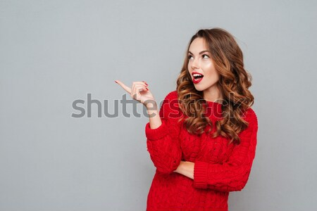 Beautiful brunette woman with good idea pointing with finger up, Stock photo © deandrobot