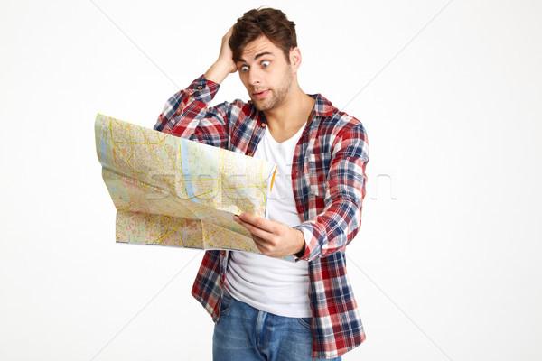 портрет молодым человеком глядя путешествия карта изолированный Сток-фото © deandrobot