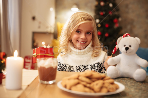 Cheerful little girl holding present and candy cane sitting at w Stock photo © deandrobot