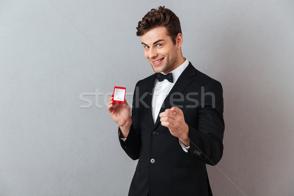 Portrait of a satisfied happy man dressed in tuxedo Stock photo © deandrobot