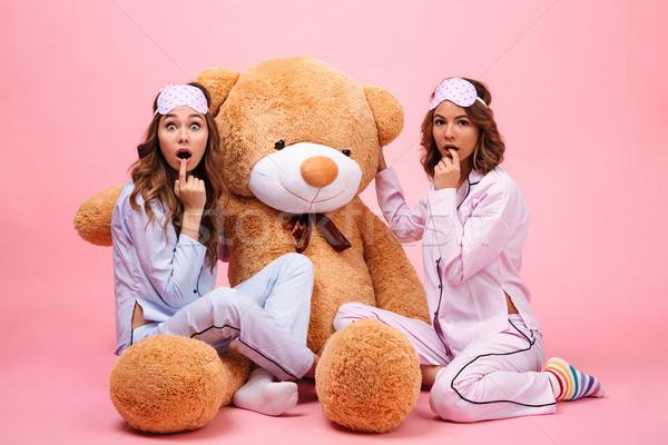 Due eccitato ragazze pigiama seduta orsacchiotto Foto d'archivio © deandrobot