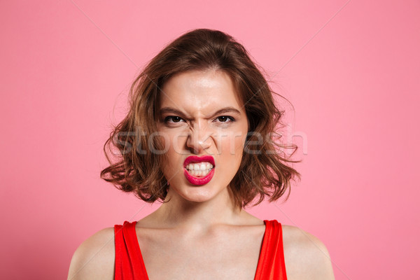 Close-up portrait of angry young woman with red lips looking at  Stock photo © deandrobot