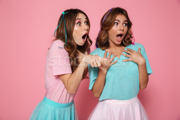Two amazed pretty girls dressed like princess pointting with fin Stock photo © deandrobot