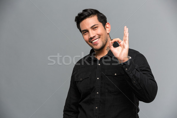 Cheerful young handsome man showing okay gesture. Stock photo © deandrobot