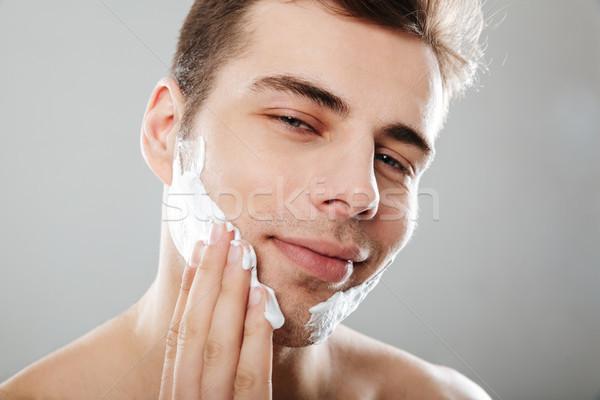 Close up portrait of a smiling man applying shaving foam Stock photo © deandrobot