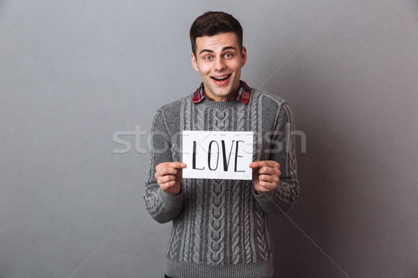 Young smiling man standing isolated holding paper with love text. Stock photo © deandrobot