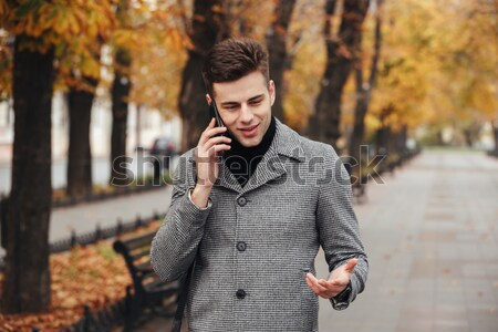Picture of young guy talking on smartmobile while looking on his Stock photo © deandrobot