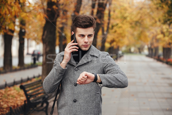 Picture of elegant man checking time with watch on hand, and spe Stock photo © deandrobot